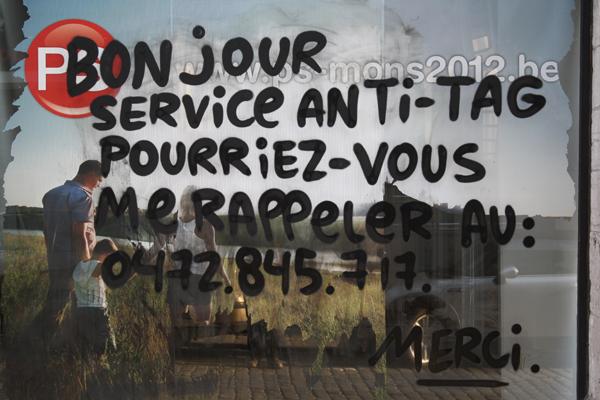 """""""Buen día servicio de limpia antigrafitis. Pueden llamarme al 0472.845.717. Gracias"""". Pinta sobre una propaganda del Partido Socialista belga en Mons. Foto: Obêtre."""